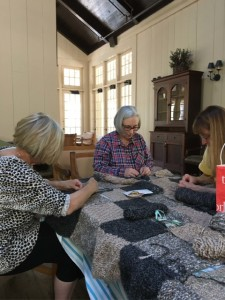 Jean Guiggio, Karen Atttaway, and Barbara Knysz (left to right) are busy sewing together the individually created rectangles that will make up the Legacy of Caring auction offering. (Photo by Mimi Zentgraf)