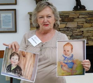 Sue Ellen Falvey shows the group her watercolors of children. (Photo by Kay Davis)
