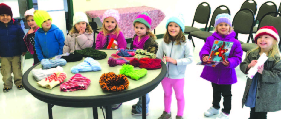 The kids at the Craddock Center look pretty pleased with the hats the Knit Togethers made to keep their little heads warm.