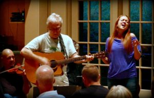 Art Shand, Bill Pound, and Hannah Stone entertain the large Acoustic Jam crowd. (Photo by Steve Papke)