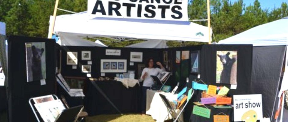 Carol Mastroianni worked the booth at the Big Canoe Artists' Oktoberfest art show. The photographs of the bears on the panels at the tent opening are Mary Joe Cox's work. (Photo by Kay Davis)